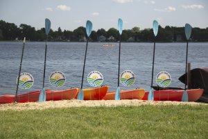 Kayaks and paddles at Brittingham Boats in front of Lake Monona