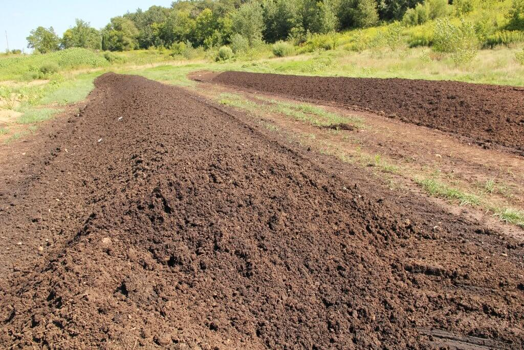 Manure composting - spreading of organic materials into windrows to dry out and become a soil-like material